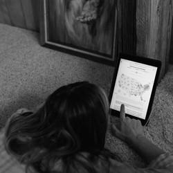 A woman scrolling through her iPad.