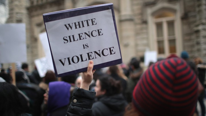 "A demonstrator holds a sign saying ""White Silence Is Violence"""