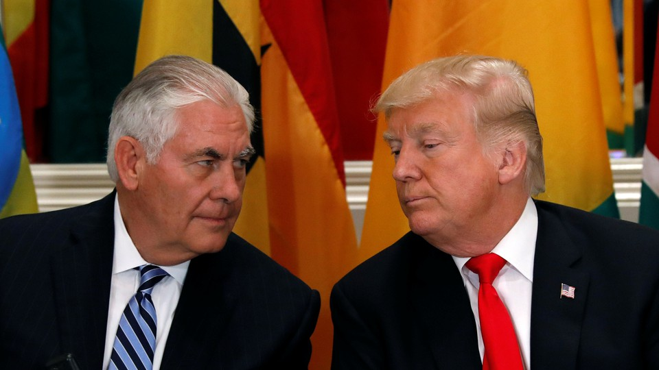 Donald Trump and Rex Tillerson are seated next to each other
