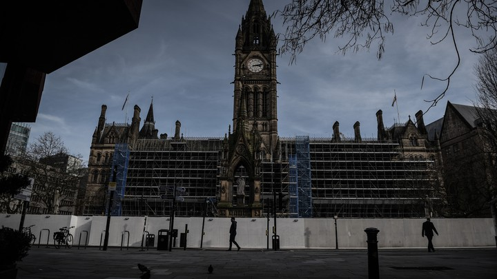 A man walks in front of Manche​ster Town Hall in the deserted​ center of Manchester after Prime Minister Boris Johnson​ imposed a lockdown on England.