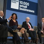 Three men and one woman in professional dress sit onstage at a panel discussion.