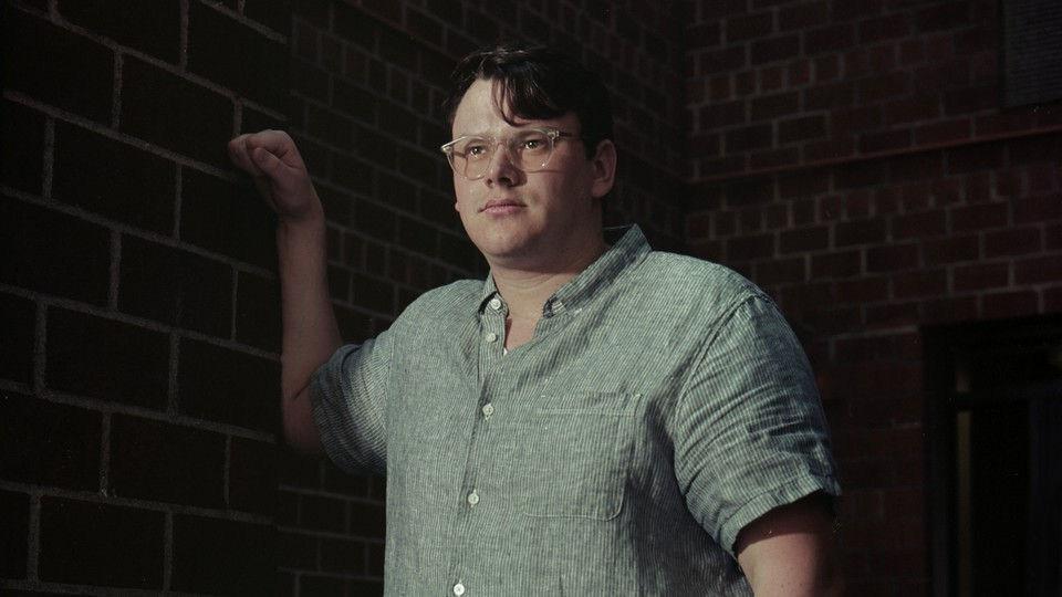 A photo of Sean McElwee, the progressive pollster and activist who is now advising Joe Biden. He is staring into the distance, wearing glasses and a light-green short-sleeve linen shirt.