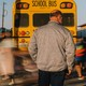 A man wearing a medical mask looks into the distance as masked students walk to school buses after class.