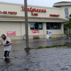 A woman walks down a flooded sidewalk in knee-high water