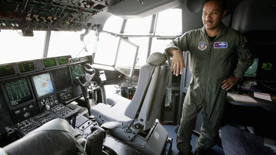 JD Haig, an Air Force Reserve pilot, stands in the cockpit of the Hurricane Hunter WC-130J, in 2007.