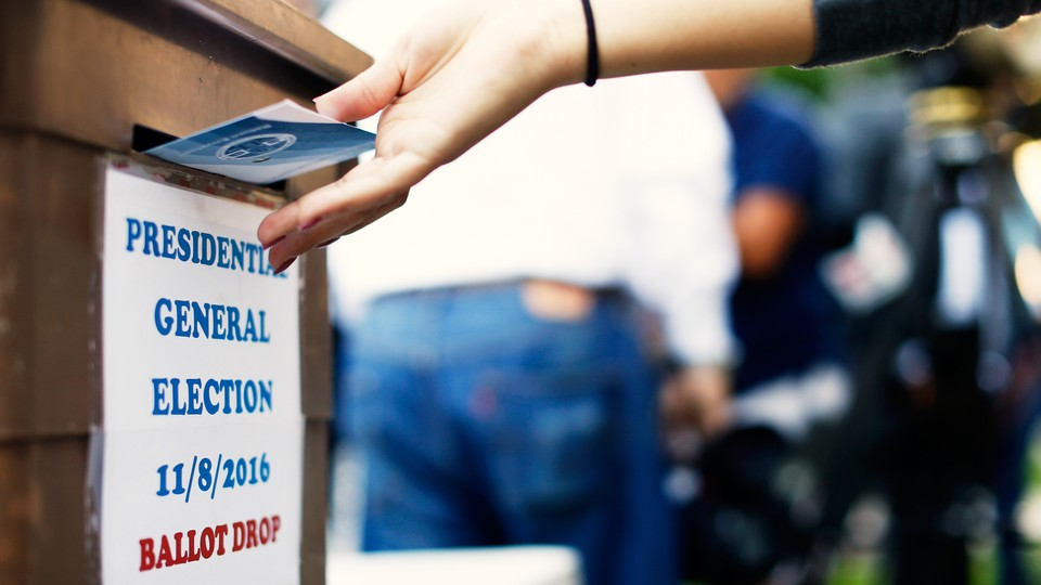 A voter dropping a ballot into a ballot box