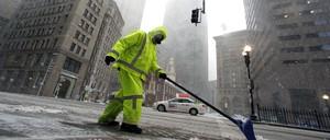 Boston city worker clears a snowy sidewalk.