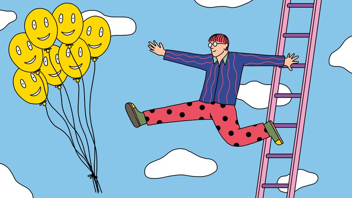 A man leaps off a ladder toward a group of happy-face balloons