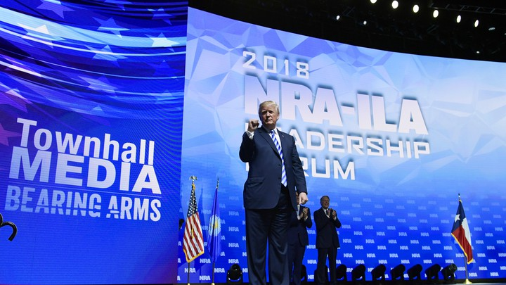 President Trump stands on a stage at the NRA convention.
