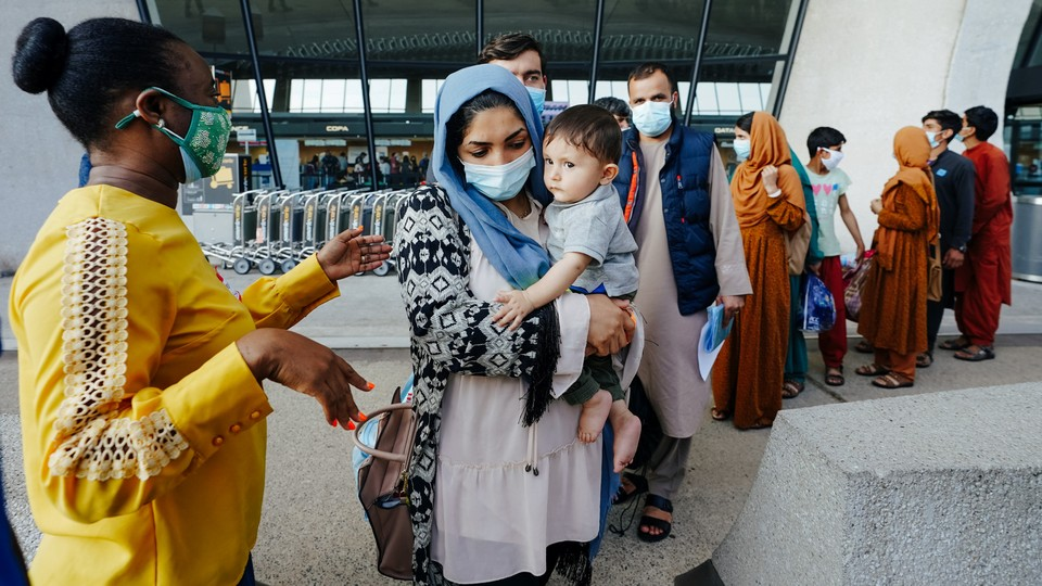 Afghan refugees line up to board a bus upon arrival at Dulles International Airport in Dulles, Virginia.