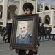 A boy carries a portrait of the Iranian Revolutionary Guard Corps general Qassem Soleimani.
