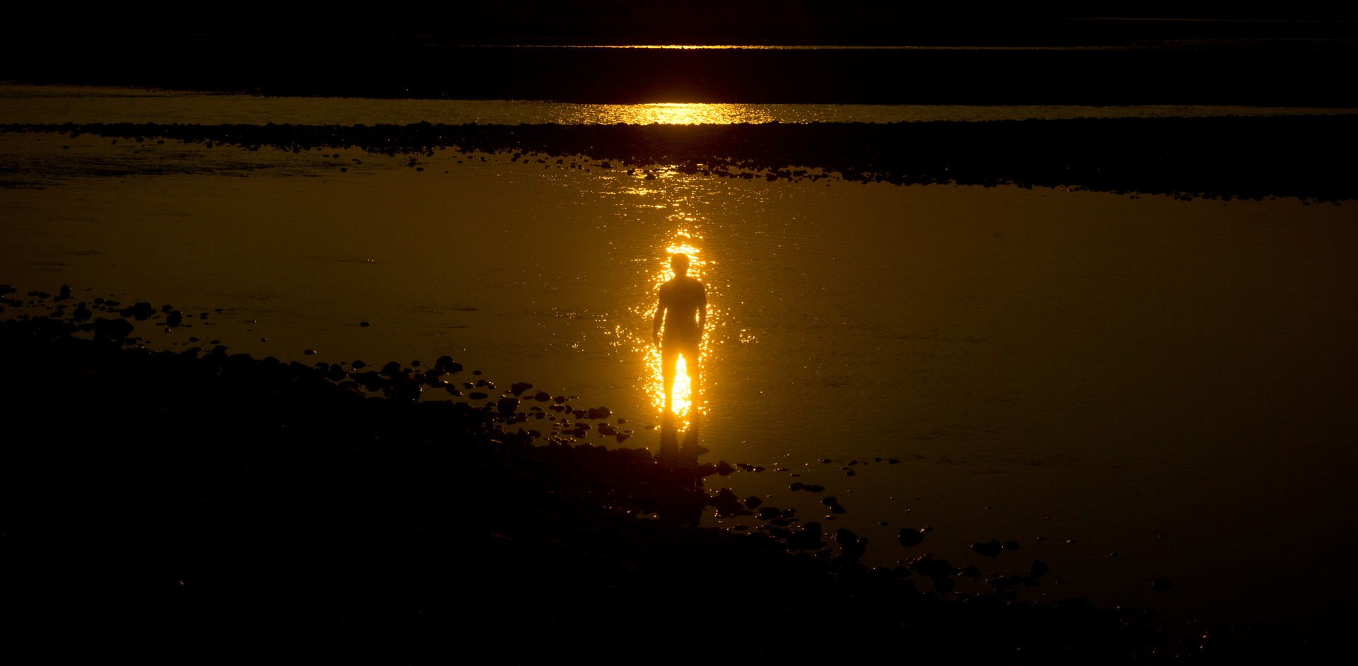 Silhouetted person and gleaming sun reflected on water