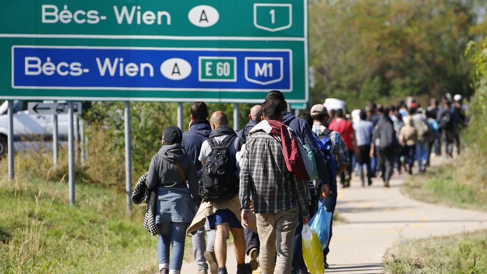Migrants walk on a road towardthe crossing point between Hungary and Austria in Nickelsdorf on September 12, 2015.