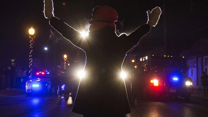 A protester raises her hands while blocking police cars