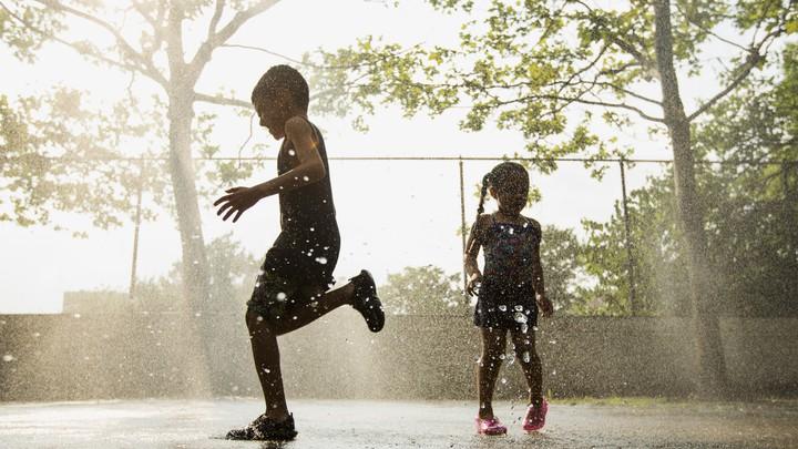 Silhouettes of children running through sprinkles
