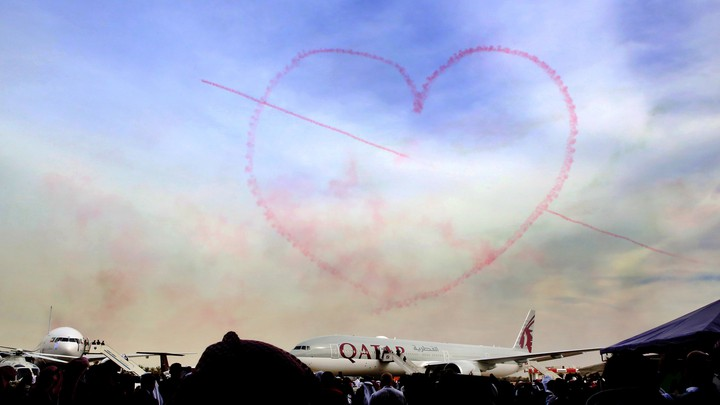 Pink smoke in the shape of a heart above an airplane