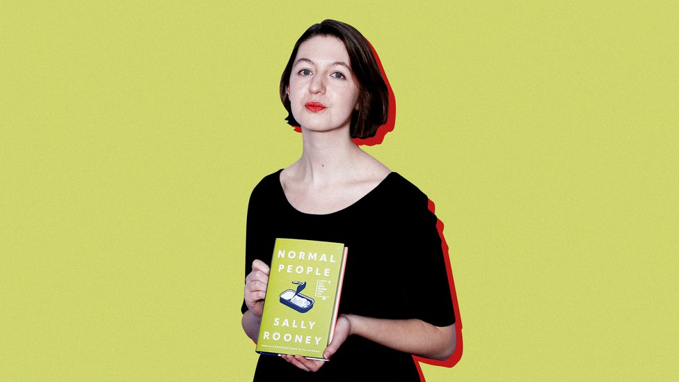 """Sally Rooney poses with a copy of her book """"Normal People"""" against a yellow background."""