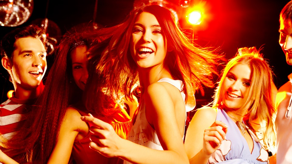 A girl laughing and dancing with her friends