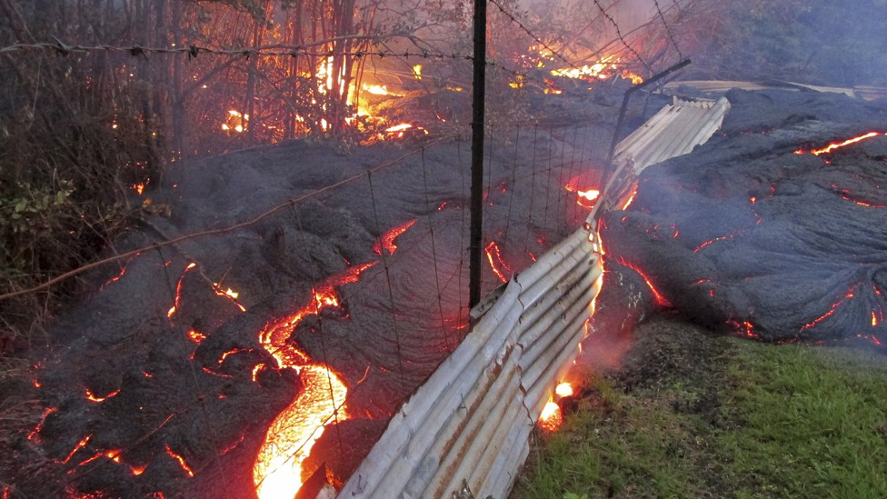 The lava flow from the Kilauea volcano moves over a fence on private property near the village of Pahoa, Hawaii, in 2014.