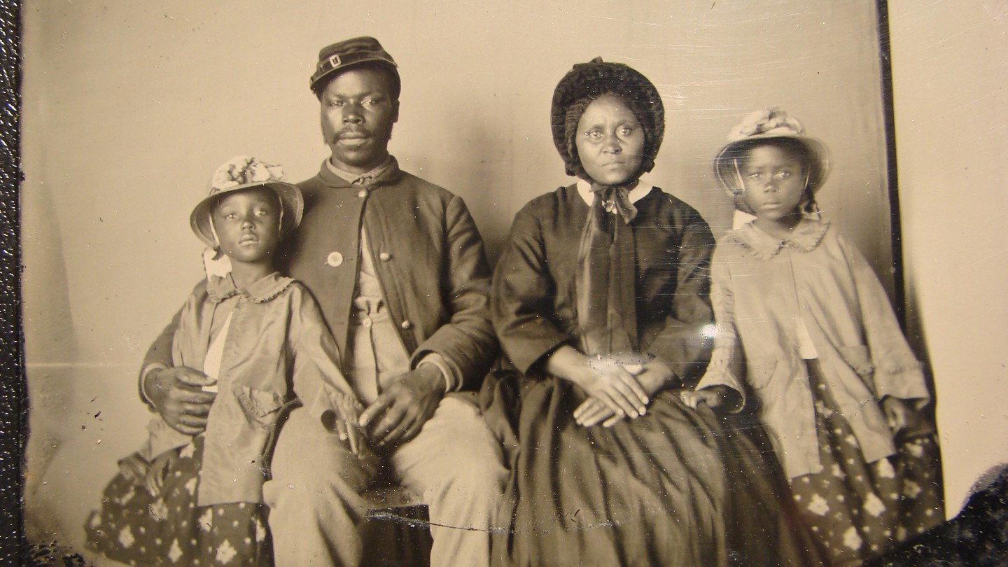 A Black Civil War soldier and his family sit for a portrait in formal clothes.