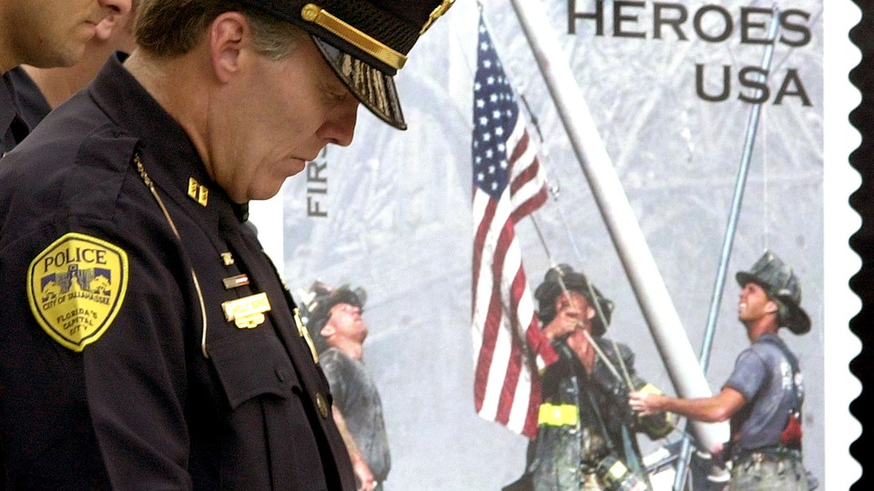 Tallahassee Police officer Kelly Burke bows his head to pray during a Sept. 11 rememberance ceremony at the Florida Capitol, Wednesday, Sept. 11, 2002.