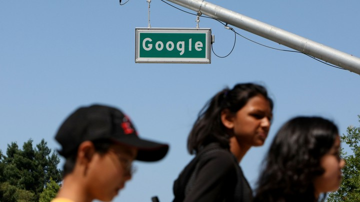 "People walk past a street sign that reads ""Google."""