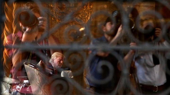 President Donald Trump, seen through a window at his Mar-a-Lago resort in Palm Beach, Florida