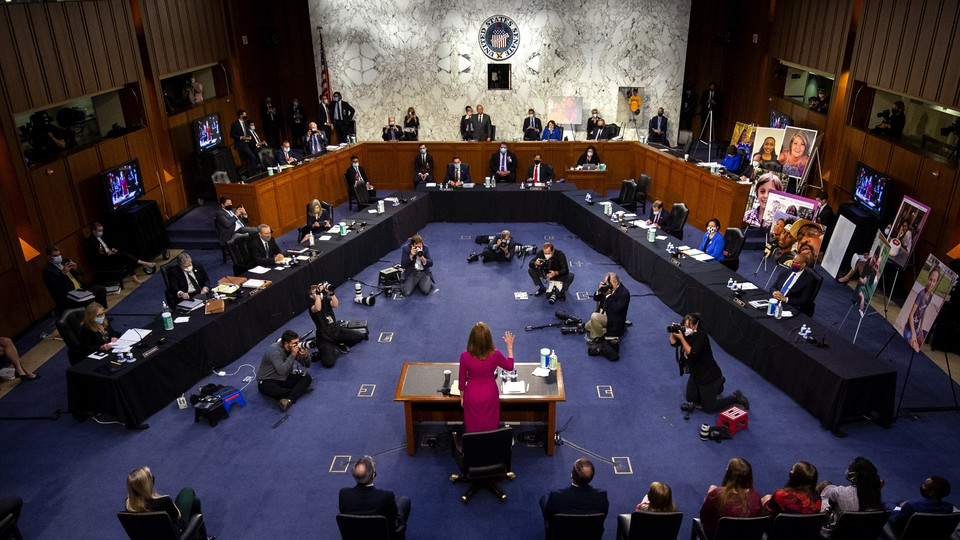 Judge Amy Coney Barrett stands with her hand raised before the Senate Judiciary Committee.