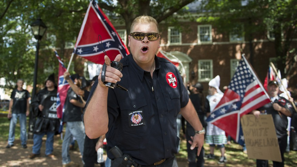 A member of the Ku Klux Klan points and shouts at counterprotesters during aJuly 2017rally in Charlottesville, Virginia. Confederate and American flags are seen in the background.