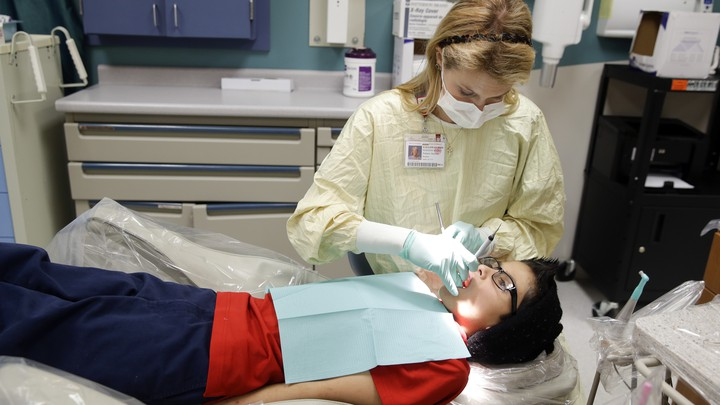 A female dentist treats a patient