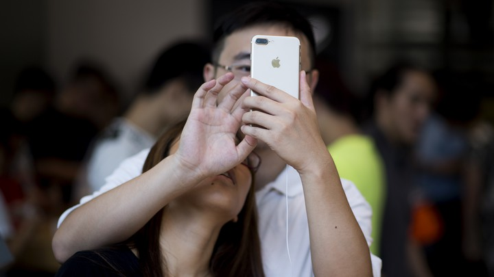 A woman leans on a man's shoulder, looking up on a phone in his hand