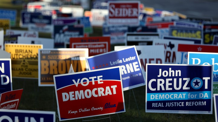 Dozens of colorful campaign signs are posted in the grass outside of a polling station on the last day of early voting in Dallas, Texas, before the 2018 midterm election.