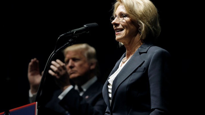 Betsy DeVos stands at a lectern in the foreground of the photo. Donald Trump is clapping behind her.