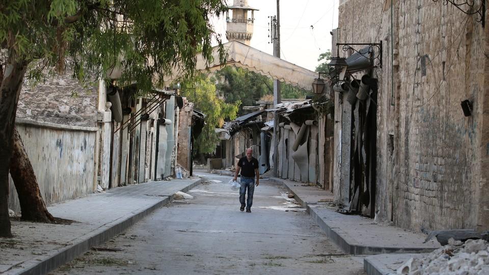 A man walks near damaged shops in the Syrian city of Aleppo