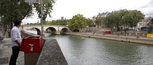 """A journalist demonstrates the proper use of a """"uritrottoir"""" on the Ile Saint-Louis along the Seine."""