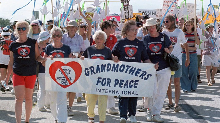 "Protesters hold a sign that says ""Grandmothers for Peace International"""
