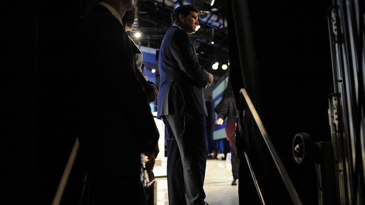 Fox News Anchor Bret Baier framed by two dark curtains on a stage