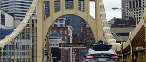 An autonomous vehicle crosses one of Pittsburgh's iconic bridges.