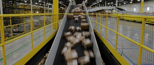 Packages on a conveyer belt in a large warehouse owned by Amazon