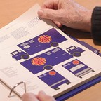 Graphic designer Burton Kramer thumbs through the pages of the CBC design standards manual he created.