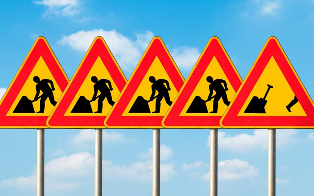 A set of five construction signs with a construction worker on each. The last sign shows the worker running away from his work.