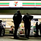 U.S. Immigration and Customs Enforcement agents serve an employment audit notice at a 7-Eleven convenience store in Los Angeles