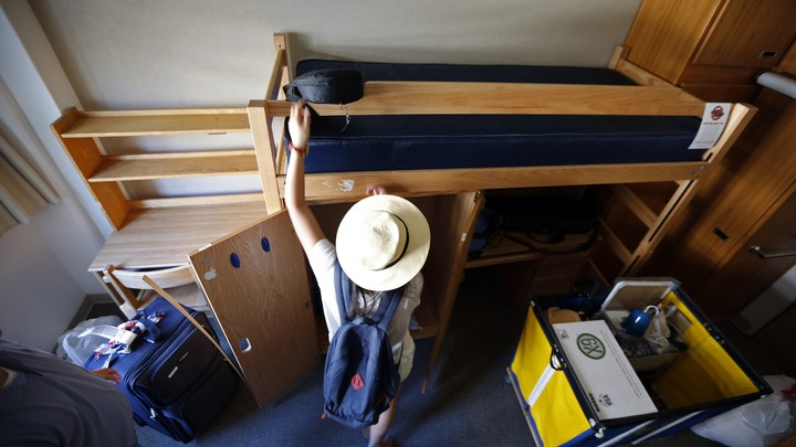 A student sets up her twin-sized bed and arranges other items in her dormitory.
