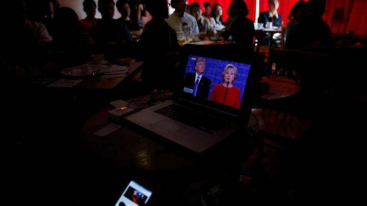 People watch direct broadcast of first U.S. presidential debate between Republican U.S. presidential nominee Donald Trump and Democratic U.S. presidential nominee Hillary Clinton at a cafe in Beijing, China, September 27, 2016.