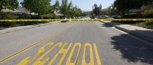 Police tape closing a street near a public school.