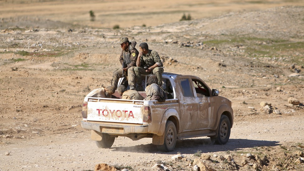 Syrian Democratic Forces fighters ride a pickup truck with Islamic State fighters held as prisoners.
