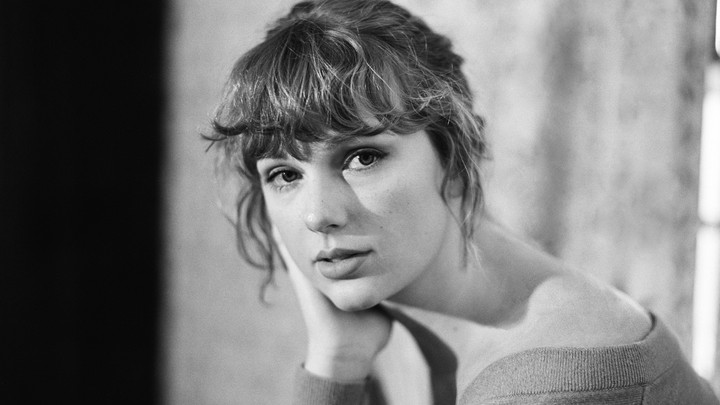 A black-and-white photo of Taylor Swift looking directly into the camera