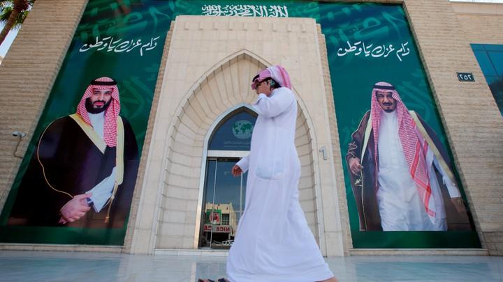 A man speaks on the phone as he walks past posters depicting Saudi Arabia's King Salman bin Abdulaziz Al Saud and Crown Prince Mohammed bin Salman.