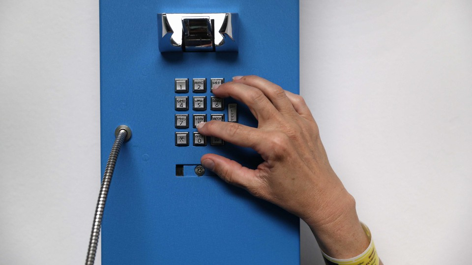 A photograph of a hand dialing on a landline phone