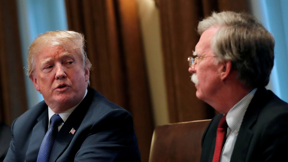 Donald Trump crosses his arms as he speaks with John Bolton.